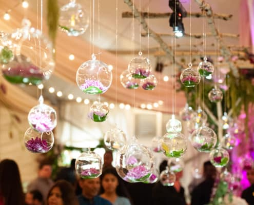 Magical wedding decor idea: suspending bright flowers in glass globes from branches