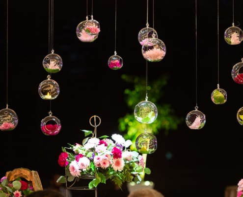 Bright purple flowers suspended from tent ceiling in glass globes: simple and creative wedding decor idea